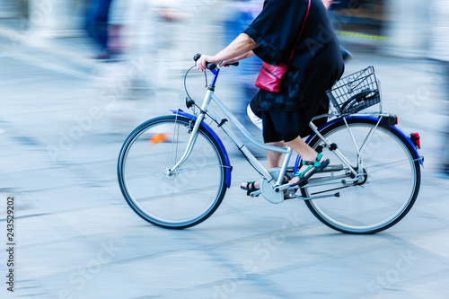 older woman rides a bicycle in the city