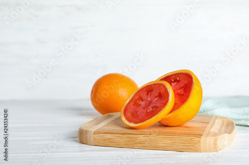 Wooden board with sliced orange revealing tomato inside on table. Think differently