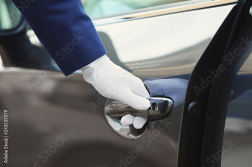 Closeup view of chauffeur opening car door Canvas Print