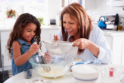 Obraz Young Hispanic girl making cake in the kitchen with her grandma, close up - fototapety do salonu