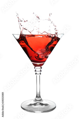 Glass of martini cocktail with splash on white background