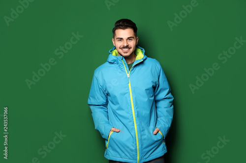 Foto auf Gartenposter Wintersport Young man wearing warm clothes on color background. Ready for winter vacation
