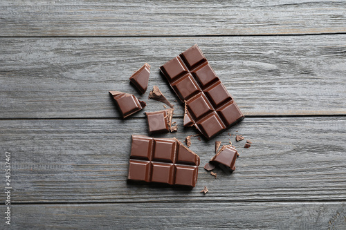 Tasty chocolate on wooden background, flat lay