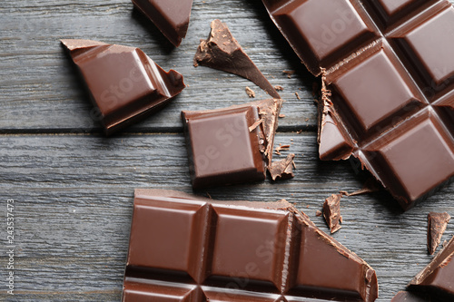 Pieces of chocolate on wooden background, top view