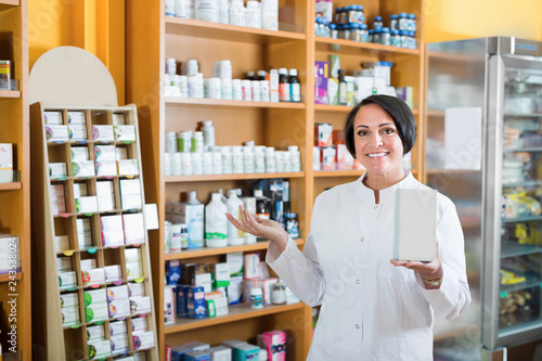 Fotografie, Obraz  Glad mature female seller with  box in pharmaceutical  store