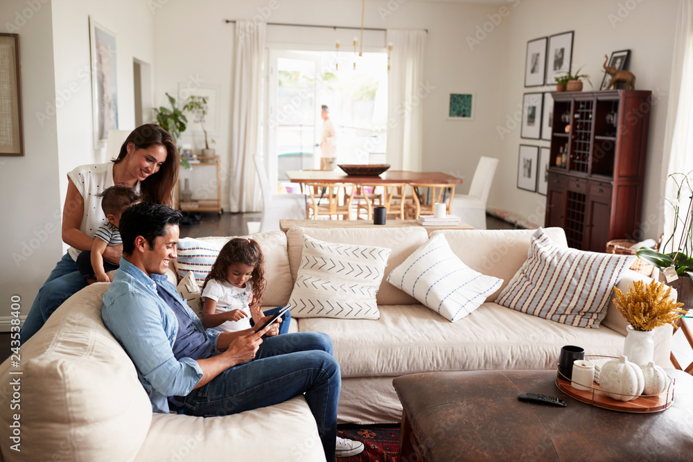 Fototapeta Young Hispanic family sitting on sofa reading a book together in their living room