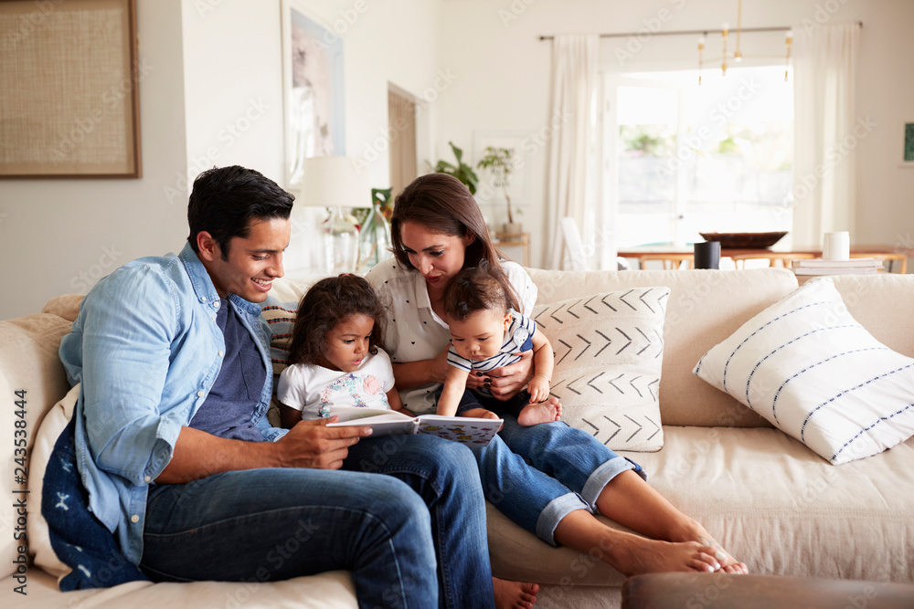 Fototapeta Hispanic couple sitting on the sofa reading a book at home with their baby son and young daughter