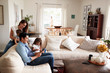 Leinwanddruck Bild - Young Hispanic family sitting on sofa reading a book together in their living room
