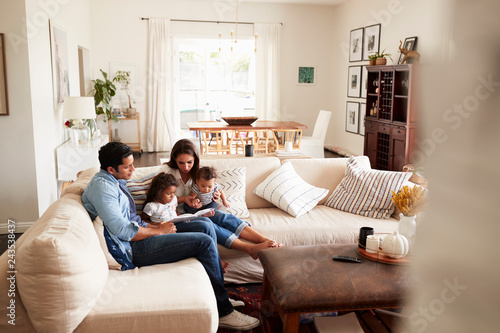 Fotografie, Obraz  Young Hispanic family sitting on sofa reading a book together in the living room