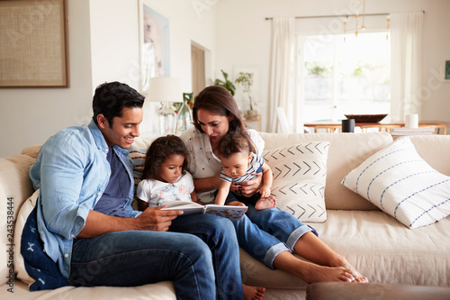 Fotografie, Obraz  Hispanic couple sitting on the sofa reading a book at home with their baby son a