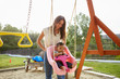 Young Hispanic mother pushing her baby on a swing at a playground in the park