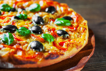 Fototapeta Do gastronomi Pizza with Mozzarella cheese, Tomatoes, pepper, olive, Spices and Fresh Basil. Italian pizza. Pizza Margherita or Margarita on wooden table background