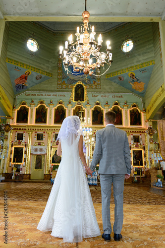 Fotografie, Obraz  Bride and groom at the church during a wedding ceremony