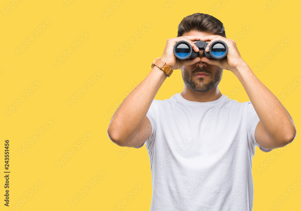 Fototapeta Young handsome man looking through binoculars over isolated background with a confident expression on smart face thinking serious