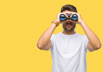 Young handsome man looking through binoculars over isolated background with a confident expression on smart face thinking serious