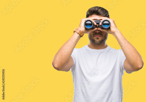 Fototapeta Young handsome man looking through binoculars over isolated background with a confident expression on smart face thinking serious obraz
