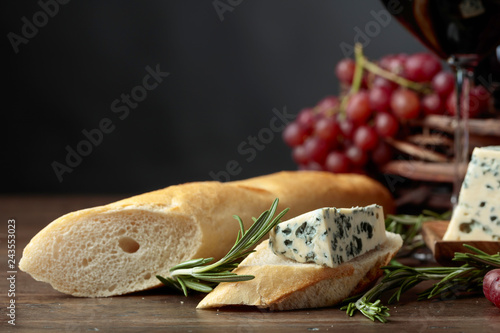 Sandwich with blue cheese and rosemary on a dark background.
