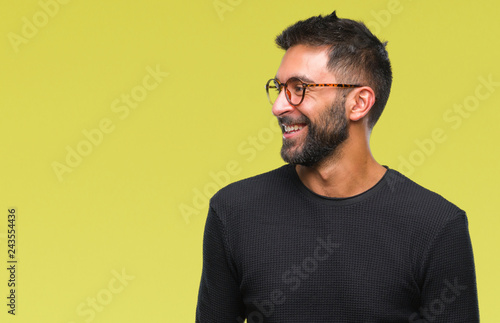 Adult hispanic man wearing glasses over isolated background looking away to side with smile on face, natural expression. Laughing confident.