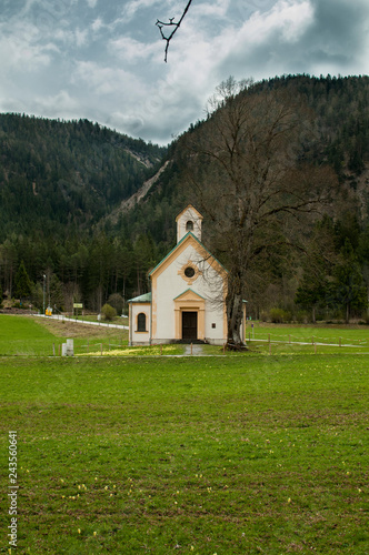 Foto  small white chapel on a meadow in the valley