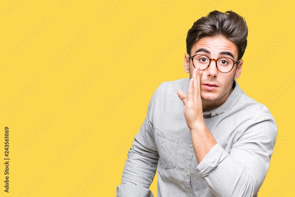 Fototapeta Young handsome man wearing glasses over isolated background hand on mouth telling secret rumor, whispering malicious talk conversation