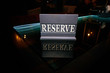 "blue wooden sign ""reserve"" stands on a black glass table"