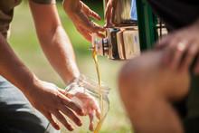 Close Up Of Men Filling Honey In Jar