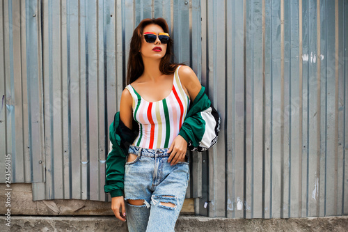 Photo  Portrait of a girl in clothes in the style of the 90s, sporty style, jacket, jeans, bananas, sunglasses