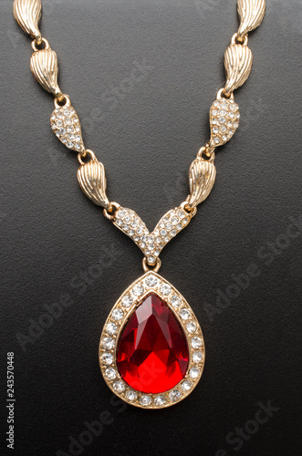 Fotografía  golden pendant with ruby and diamonds isolated on black macro