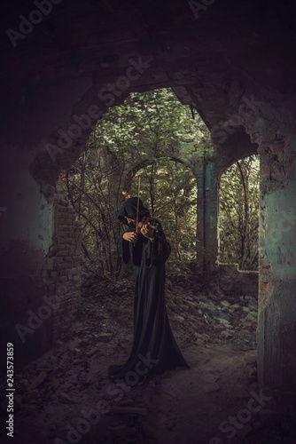Photo  Lonely man in a cloak composing music, playing violin in an old abandoned castle