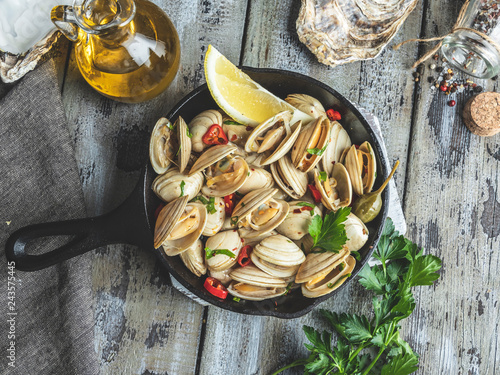 Vászonkép Cooked seafood clams in the iron pan portion with lemon and seasoning
