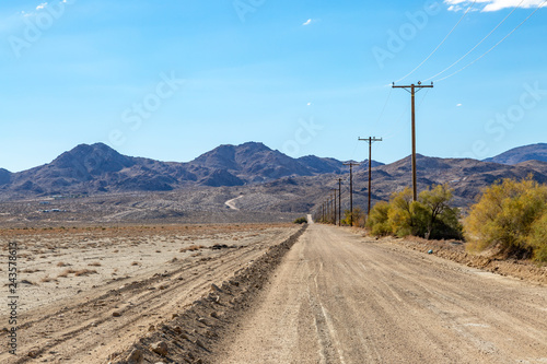 An unpaved road in the Californian desert, with rugged hills in the distance Poster Mural XXL