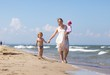 Woman and her kids walking on sea shore at sunny summer day