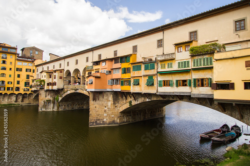 Fotografie, Obraz  The Shopping Bridge with Boats Moored - Boats await their customers under colorful Ponte Vecchio - a bridge hosting many jewelry shops - that crosses the River Arno