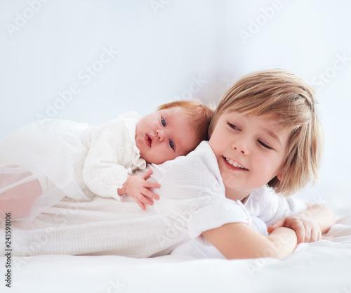 Fotografia newborn baby sister lying on cute elder brother