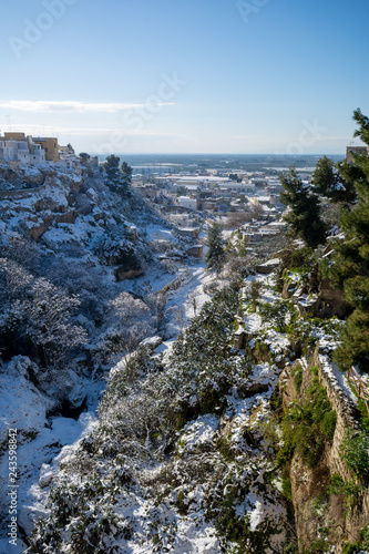 Vászonkép Vertical View of the Gravina of the Town of Massafra, Covered by Snow on Blue Sky Background