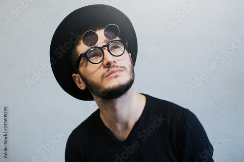 Fotografie, Obraz  Portrait of bearded hipster guy looking up, wearing sunglasses and black hat, over white background