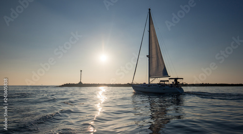 Sailboat going past jetty in the Channel Islands harbor in Oxnard California United States