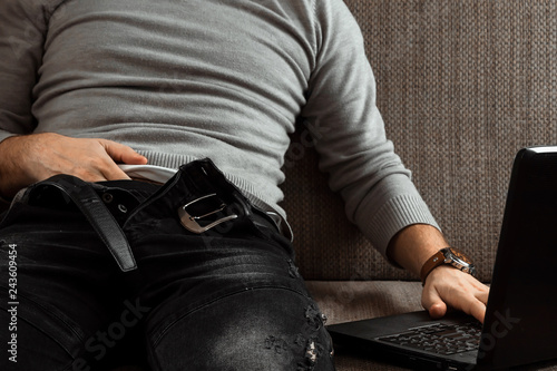 A man watches an adult video on a laptop while sitting on the couch. The concept of porn, masturbation, male needs, pervert, lust, desire, loneliness. - 243609454