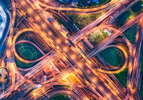Aluminium Prints Night highway Aerial view over complicate intersection road and express way in Bangkok Thailand at night with long exposure vehicle light trail. Shot by drone.