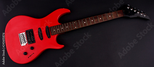 Photo  Red electric guitar with a black background.