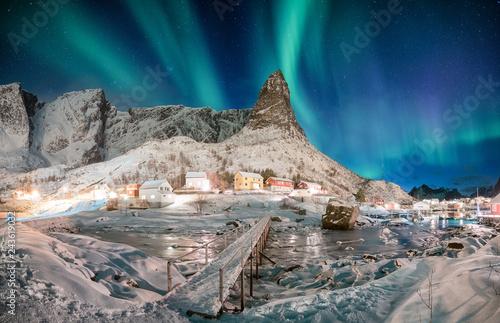 Foto auf Gartenposter Nordlicht Landscape of snowy mountain with aurora borealis in scandinavian village