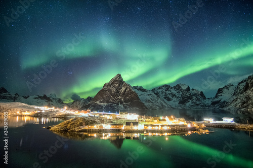Aurora borealis over mountains in scandinavian village glowing