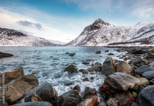 Foto op Aluminium Purper Seascape wave hitting rocks with mountains on arctic coastline