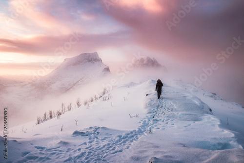 Obraz na płótnie Man mountaineer walking with snow footprint on snow peak ridge in blizzard