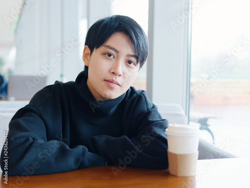 Photo  Portrait of cute beautiful young lesbian with short haircut and trendy boyish clothes sitting in coffee shop, friendly Chinese gay girl