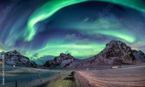 Photo sur Toile Aurore polaire Northern lights explosion on snowy mountain range