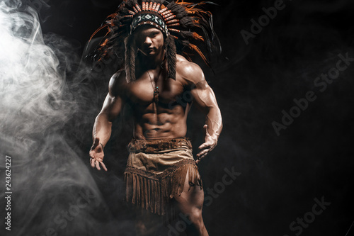 Photo American Indian Apache warrior chief  in traditional clothing and feathered headdress with weapon