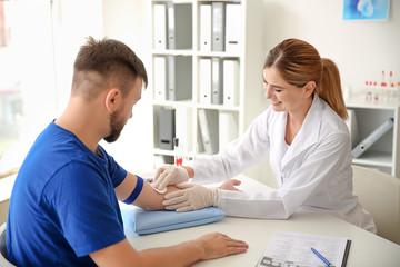 Liječnik koji priprema pacijenta za vađenje krvi u klinici
