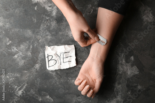 Fotografie, Tablou  Woman cutting veins with razor blade and death note with text BYE on grey background