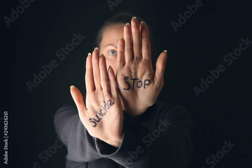Text STOP SUICIDE written on palms of woman against dark background Fototapet